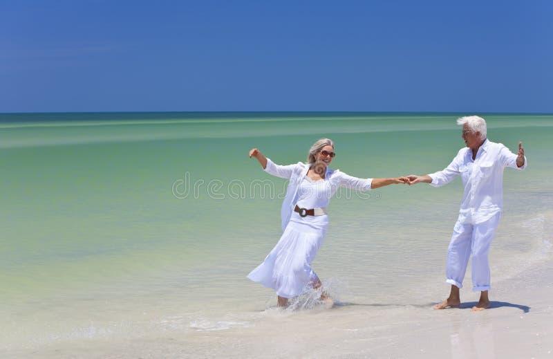 Dancing maggiore felice delle coppie sulla spiaggia tropicale fotografie stock libere da diritti