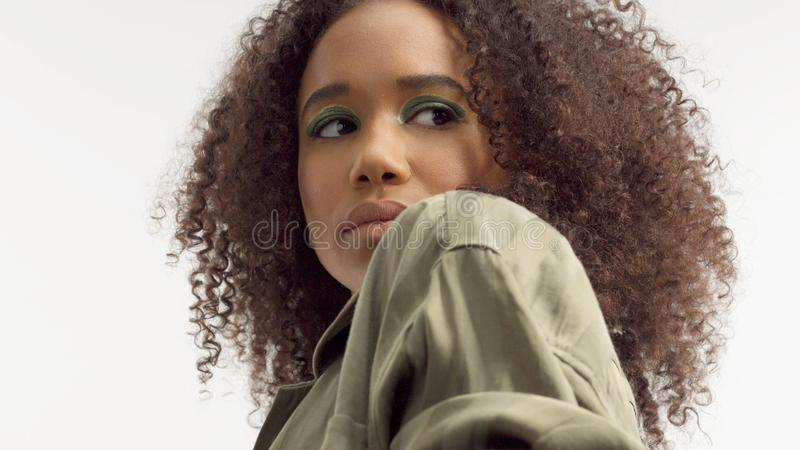 Closeup portrait s of young mixed race model with curly hair in studio with green metallic eyeshadows stock photos