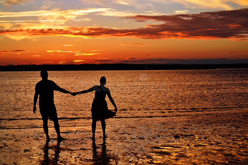 Dancing at the ocean. A silhouette of a couple dancing at the ocean during sunset. Taken at Hills Beach in Biddeford, Maine royalty free stock photo