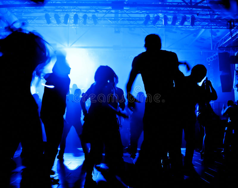 Dancing people in a disco. In front of bright disco lights royalty free stock photos