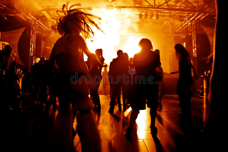 Dancing people in a disco. In front of bright disco lights royalty free stock photography