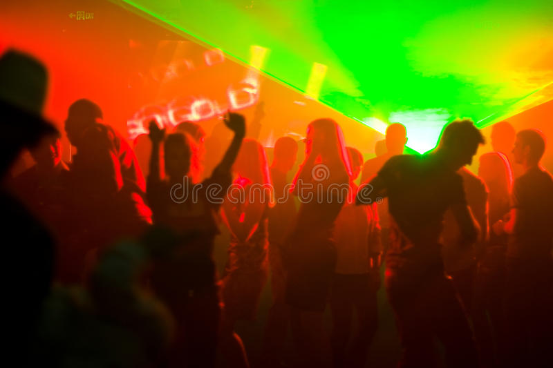 Dancing people in red disco light royalty free stock image