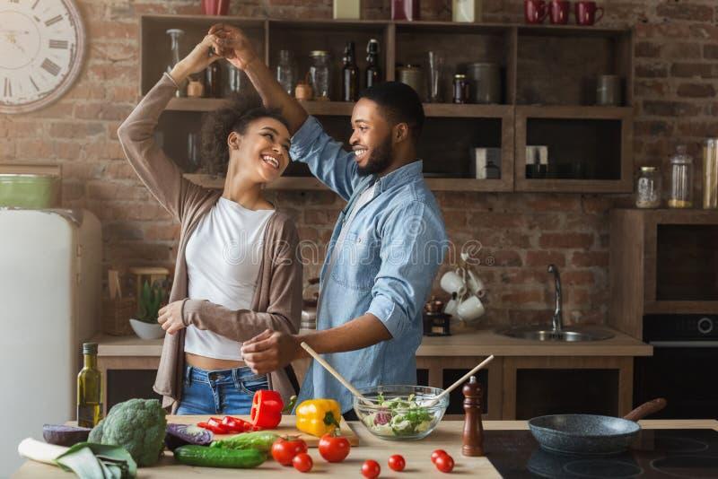 Dancing romantico felice delle coppie nella cucina mentre cucinando immagine stock libera da diritti