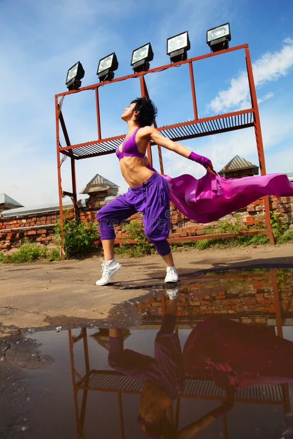 Dancing sottile della ragazza con il kerchief sul tetto immagine stock
