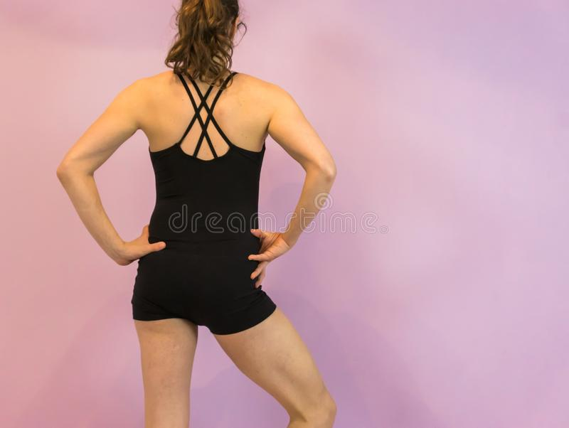 Dancing sport fashion, a young transgender girl wearing a black leotard with crossed back royalty free stock image