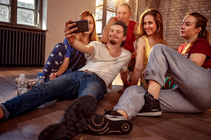 dancing, sport and urban culture concept - Group of smiling dancers taking selfie stock photography