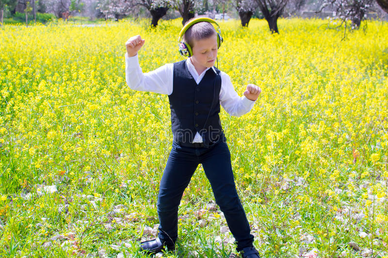 Dancing in the spring field. Boy dancing in the spring flower field listening to music royalty free stock photos