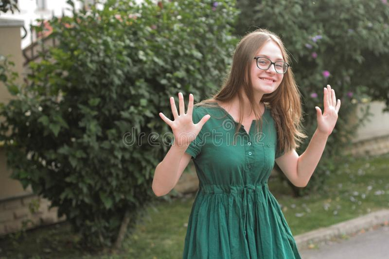Dancing teen age girl in glasses and green dress, having fun. Summer, outdoor background. Copy space royalty free stock photo