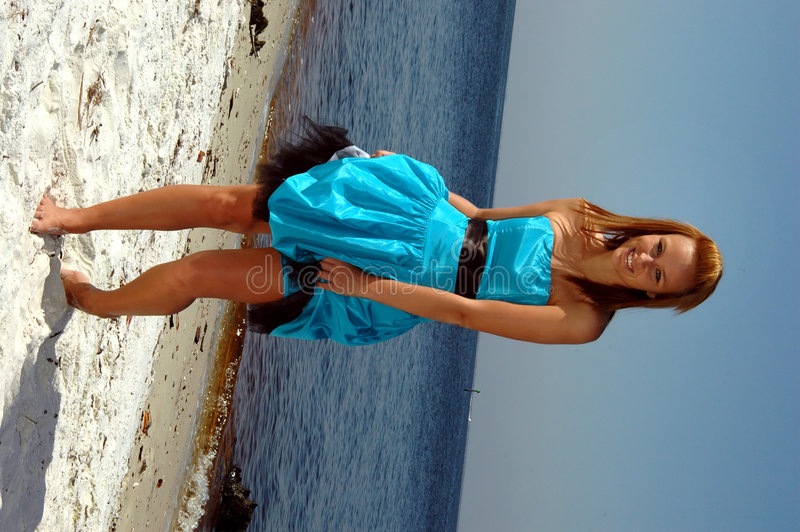 Dancing teen on beach. A teenager dancing on the beach in her formal prom dress stock image