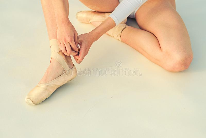 Dancing on toes. Lacing ballet slippers. Female feet in pointe shoes. Ballerina shoes. Ballerina legs in white ballet. Shoes. Pointe shoes worn by ballet dancer stock photo