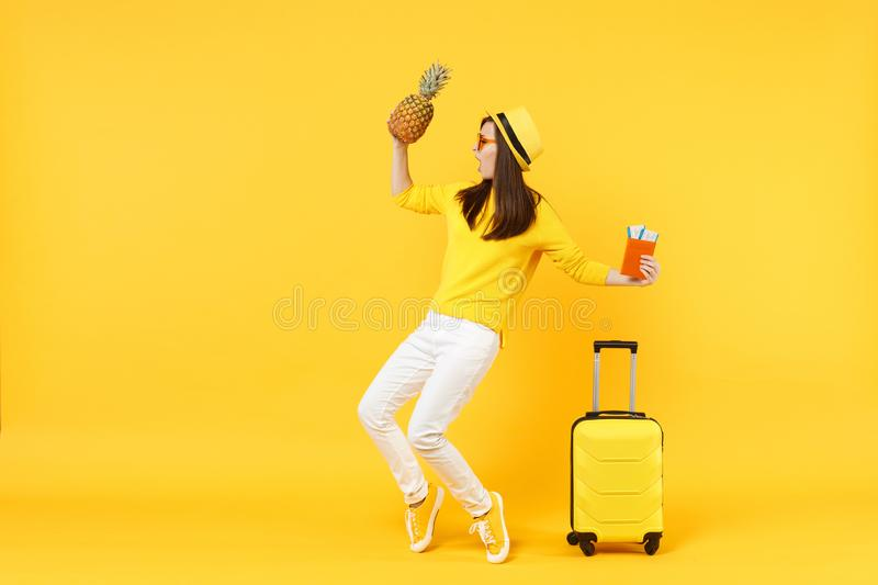 Dancing traveler tourist woman in hat holding passport tickets, fresh pineapple fruit isolated on yellow orange. Background. Passenger traveling abroad on stock photography
