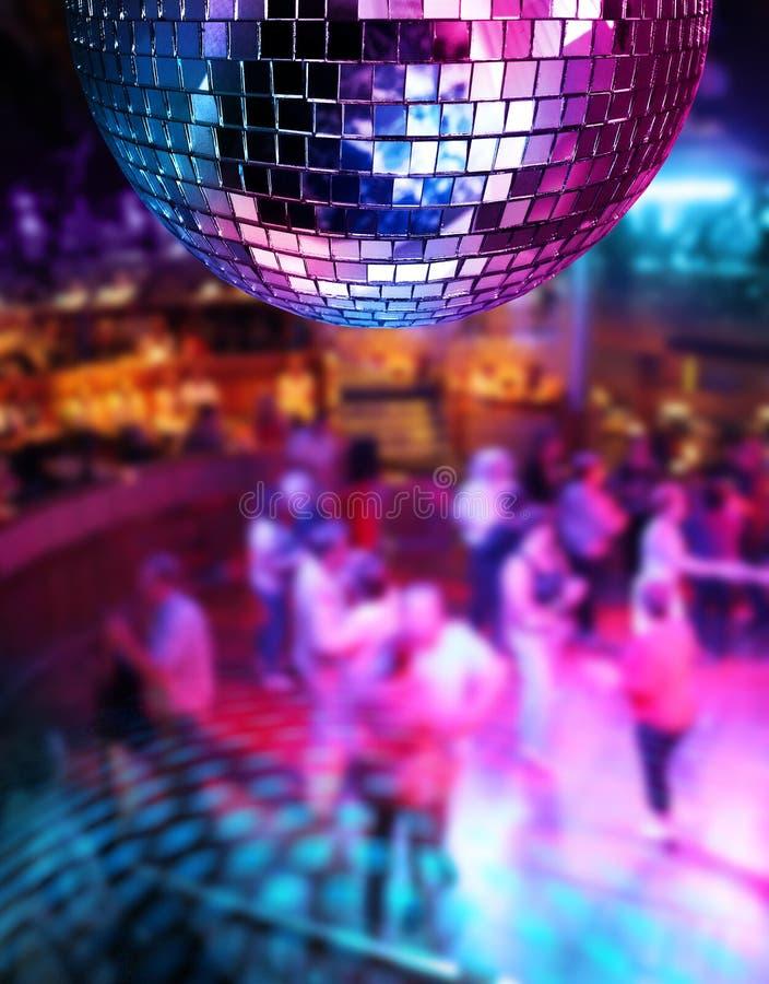 Dancing under disco mirror ball. People dancing under colorful lights of disco mirror ball