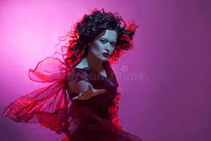 Dancing woman with flying red dress. Beautiful Gothic girl like a witch. She dancing and wavered dress stock photography