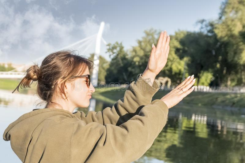 Dancing woman at the river. Beautiful woman in sunglasses dancing near the river stock photography