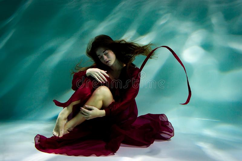 Woman under the water in a red dress. stock photography
