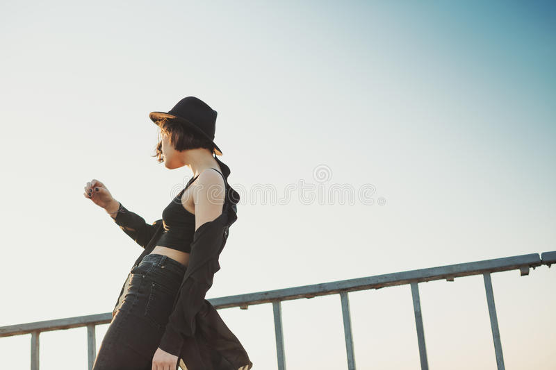 Dancing young woman in the black clothes and hat. Profile slim. Sunset sky background stock image