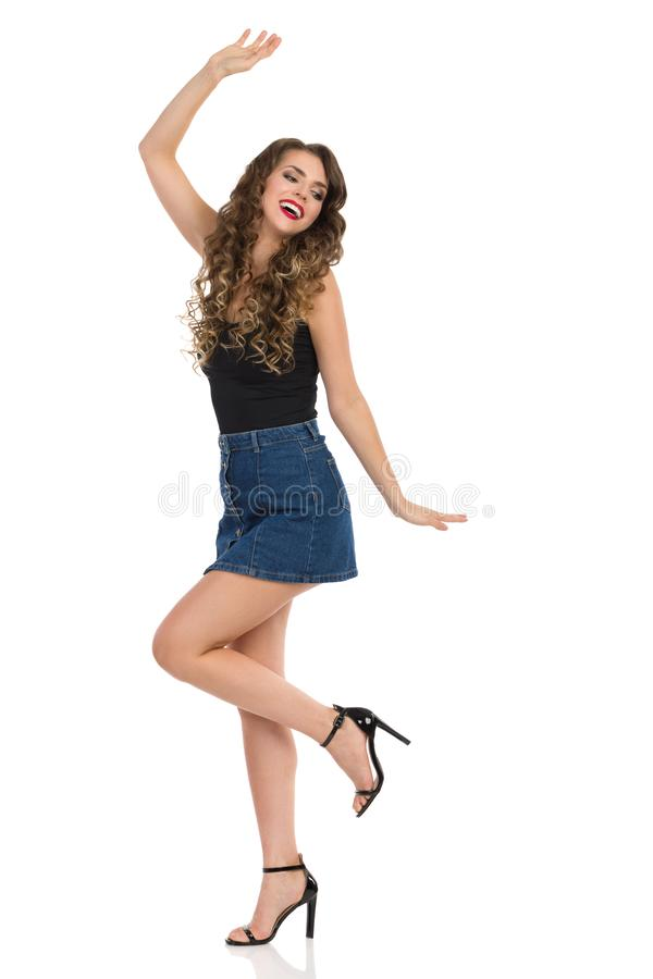 Dancing Young Woman In Jeans Mini Skirt And High Heels. Carefree young woman in jeans mini skirt, black top and high heels is dancing and smiling. Side view stock photo