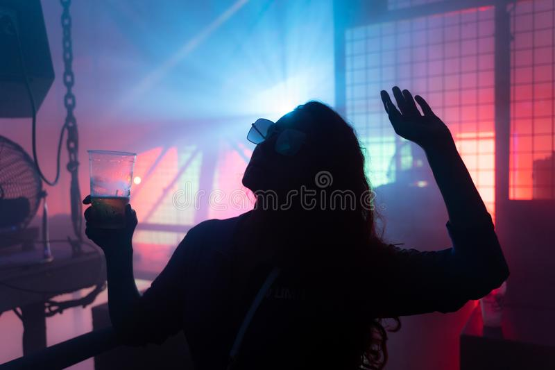 Dancing young woman silhouette at techno club stock photo
