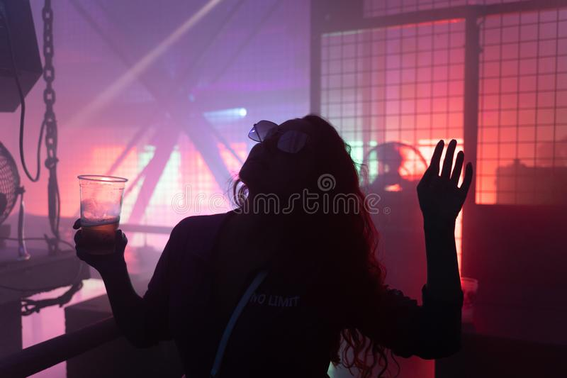 Dancing young woman silhouette at techno club.  royalty free stock images