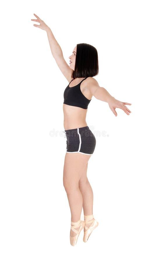 Dancing young woman standing tiptoe stock image