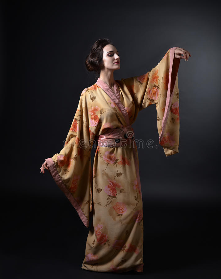 Dancingowa kobieta w tradycyjnym Japońskim kimonie na czarnym tle fotografia royalty free