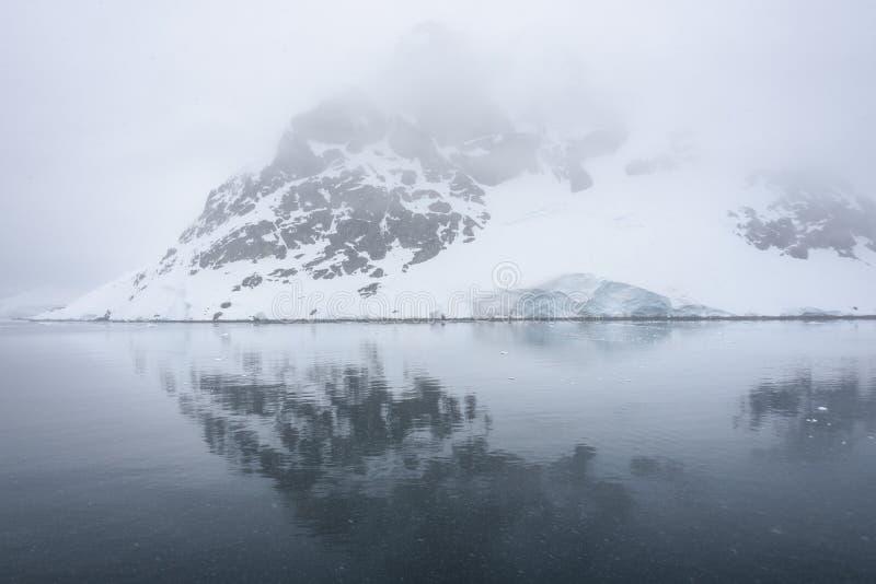 Danco海岛,积雪和覆盖在与反射的雾在南极洲的水域中 图库摄影