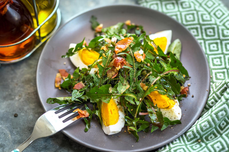 Dandelion salad with eggs and bacon stock photo