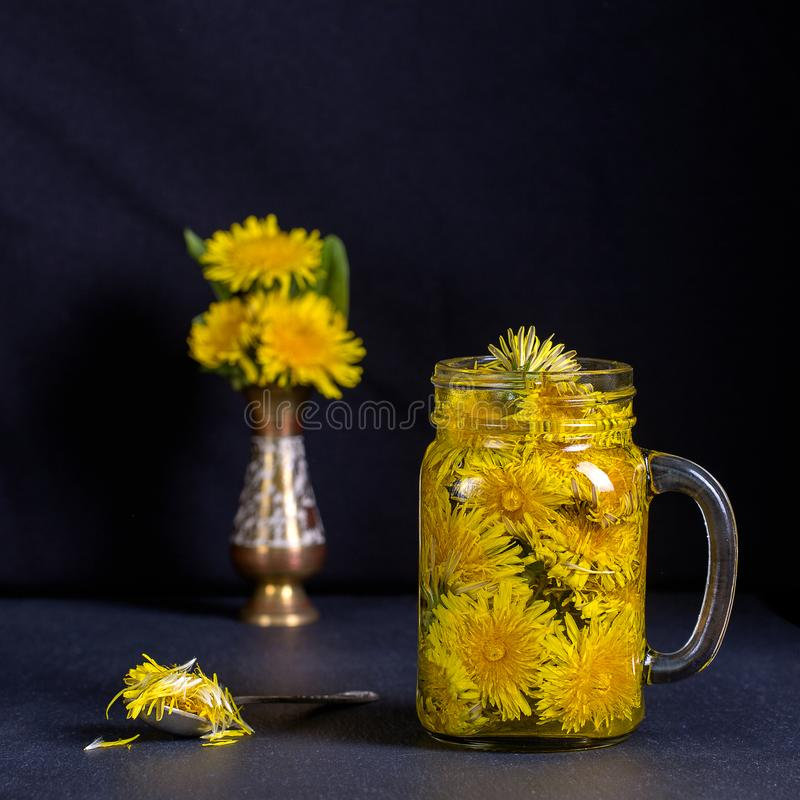 Dandelion yellow flower tea drink in glass mug on black background. Concept of healthy eating. Dandelion yellow flower tea drink in glass mug on black background stock photography