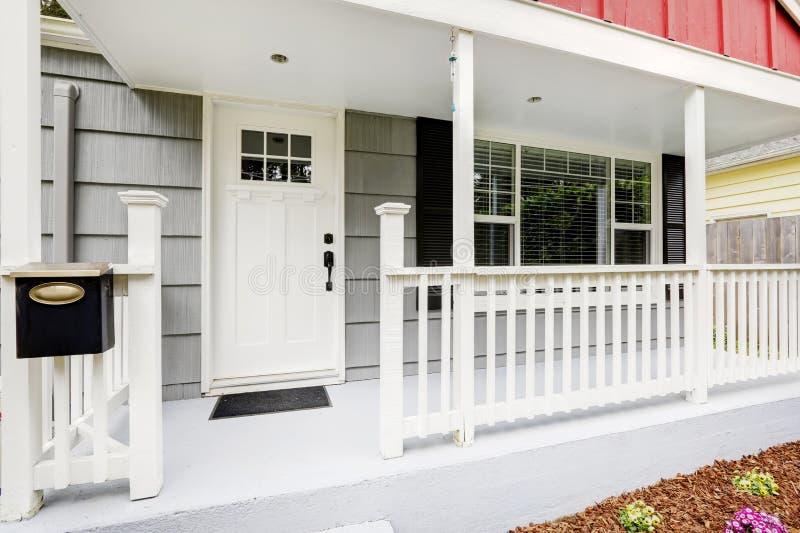 Dando boas-vindas ao pátio de entrada coberto vangloria-se da porta da rua branca pura foto de stock royalty free