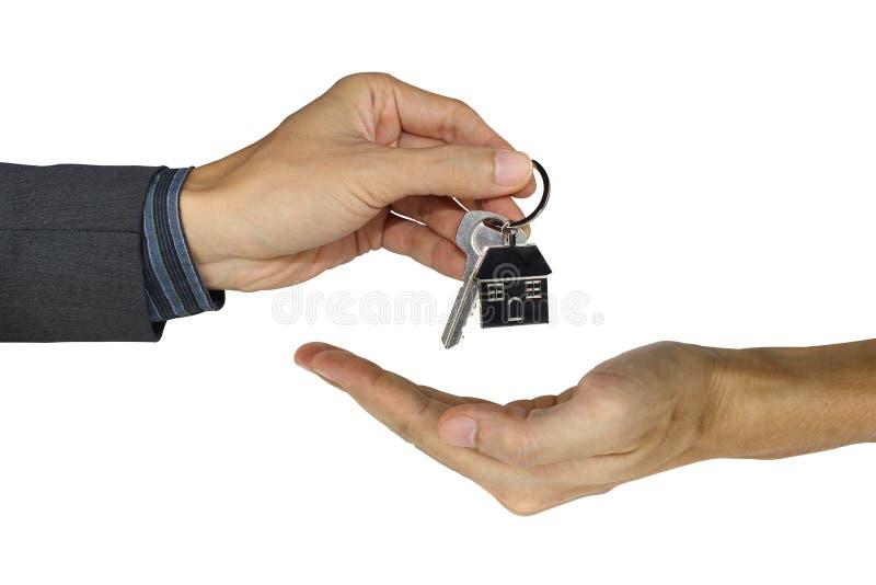 Dando las llaves de la casa aisladas en el fondo, el concepto de la propiedad, la hipoteca y el concepto blancos del agente fotos de archivo
