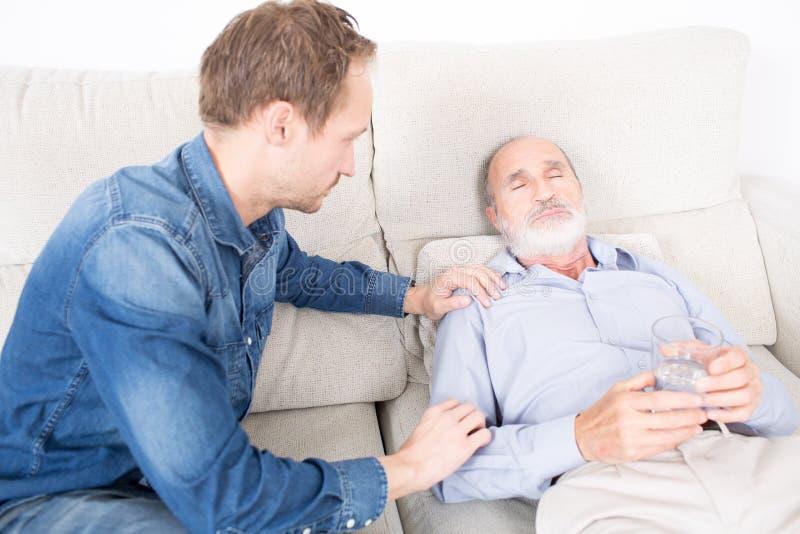 Dando a medicamentação a um homem idoso fotos de stock royalty free