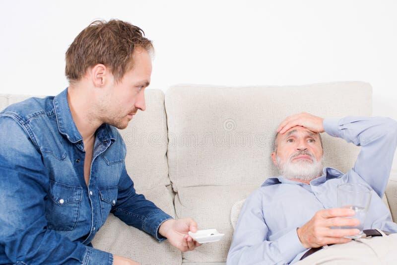 Dando a medicamentação a um homem idoso imagem de stock