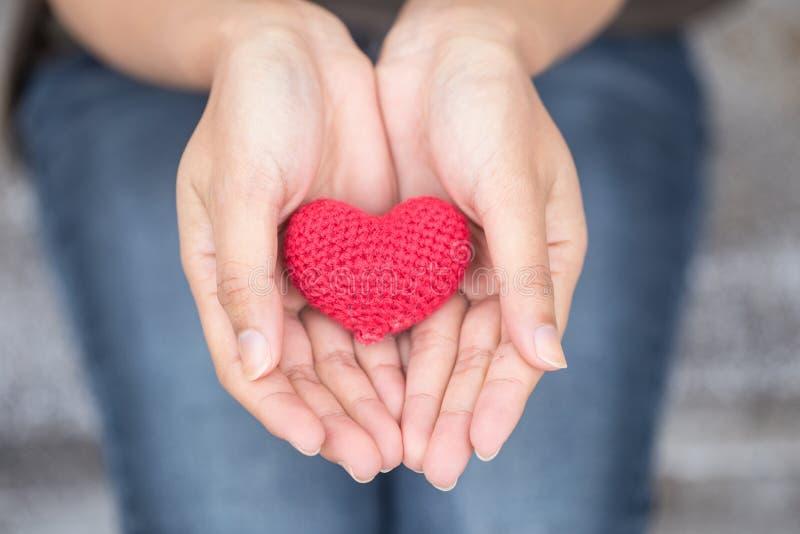 Dando o amor Coração vermelho na mão das mulheres imagens de stock