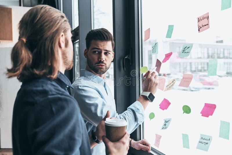 Dando o conselho do negócio Dois colegas novos no wea ocasional esperto imagem de stock