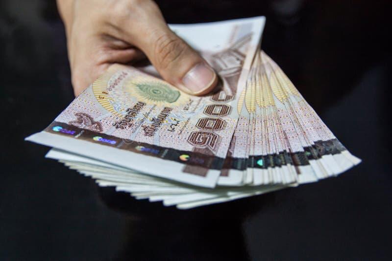 Dando o dinheiro, dinheiro tailandês, baht 1000 fotos de stock royalty free
