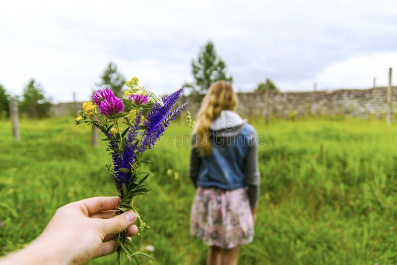 Dando o ramalhete consideravelmente feito a mão da flor a uma menina fotos de stock