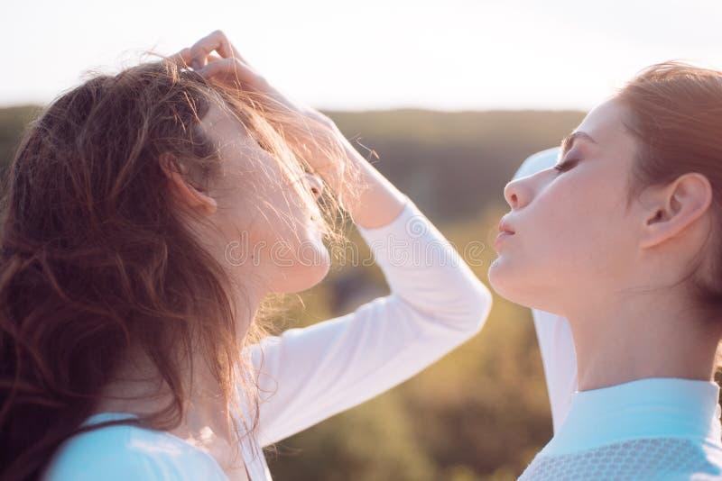 Dando a pelo su fuerza Adolescentes con el peinado ondulado natural Muchachas lindas con el peinado largo Mujeres jovenes con fotografía de archivo