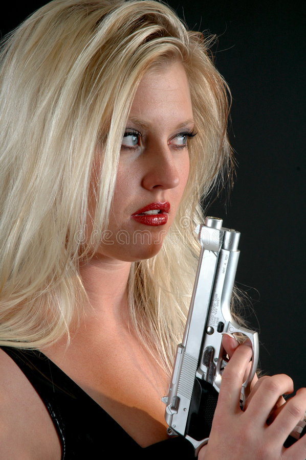 Danger. A beautiful blond woman with a gun stock photos