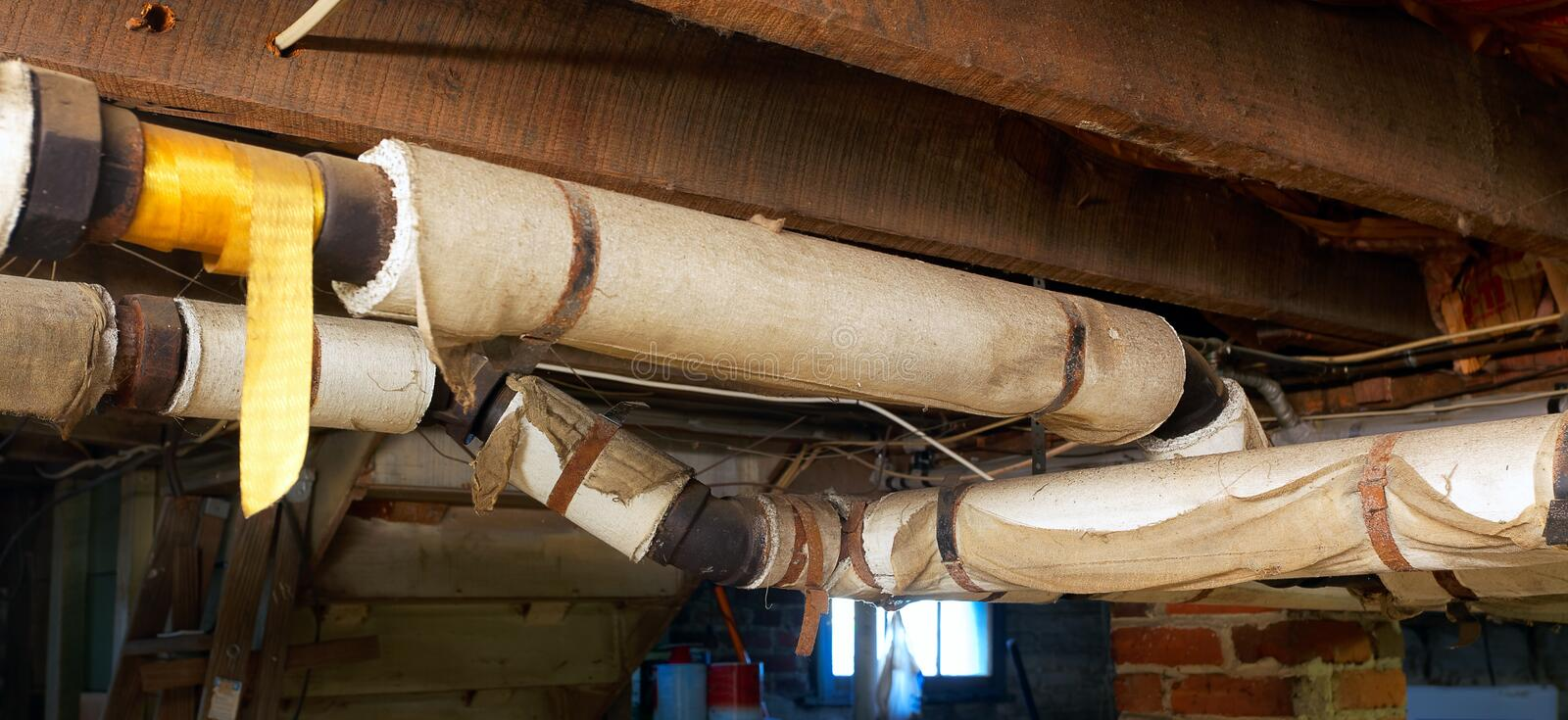 Danger! Asbestos!. Basement plumbing pipes wrapped with asbestos insulation royalty free stock photography