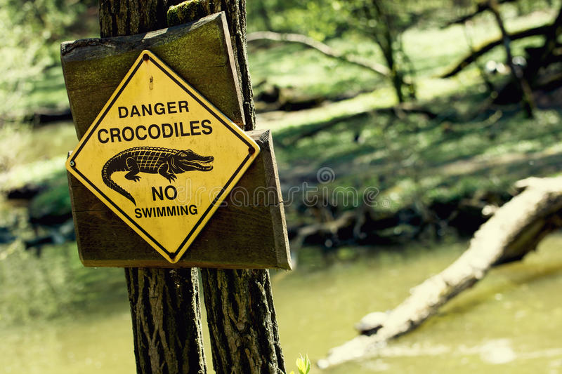 Danger crocodiles, no swimming. Caution in nature stock image