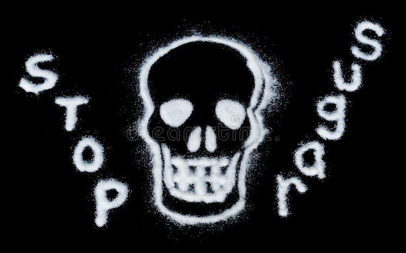 Danger de sucre Nuisez au concept de sucre blanc formant un crâne Le texte étant isolé sur un fond noir photos libres de droits