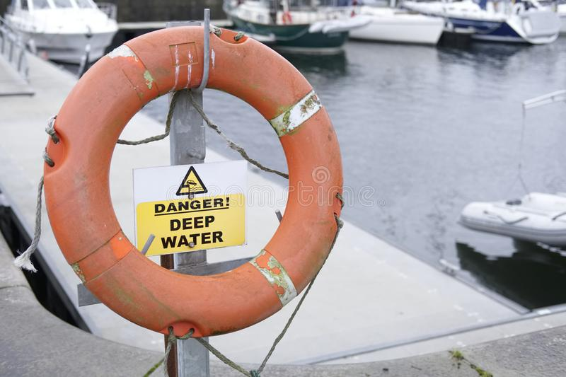 Danger Deep Water Sign with Orange Rubber Safety Ring. Round orange rubber safety ring at marina warning of danger deep water with sign on post royalty free stock image