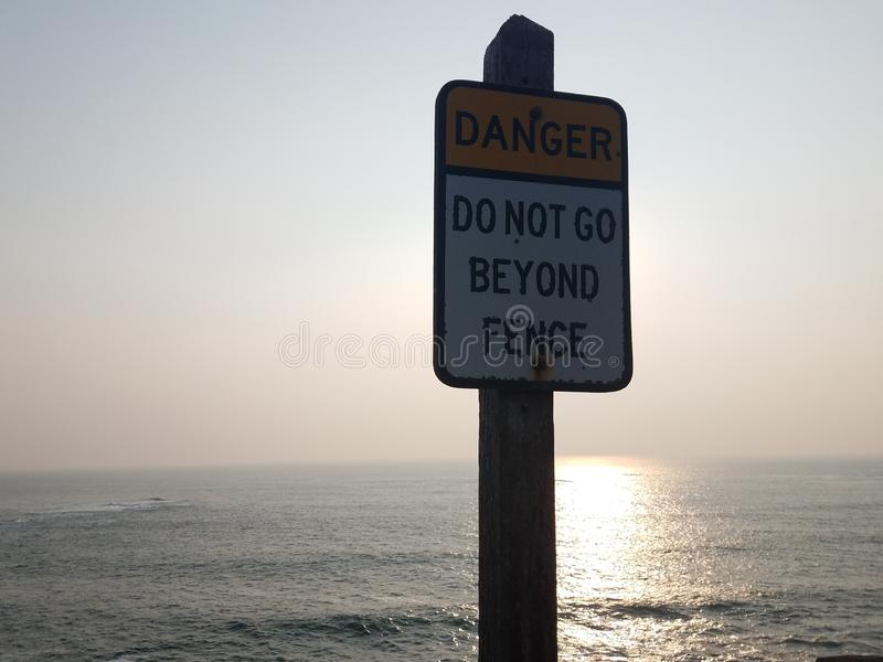 Danger do not go beyond fence sign and ocean. Or sea royalty free stock image