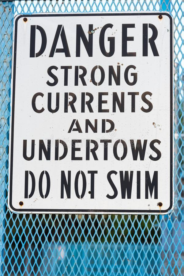 Danger do not swim sign warning of strong currents and undertows. Black and white sign mounted on blue fencing warning of strong currents and undertows in nearby stock image
