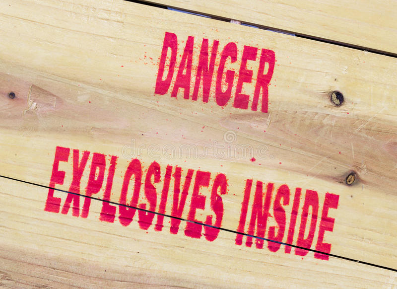 Danger explosives. Warning message on wooden plate royalty free stock photography