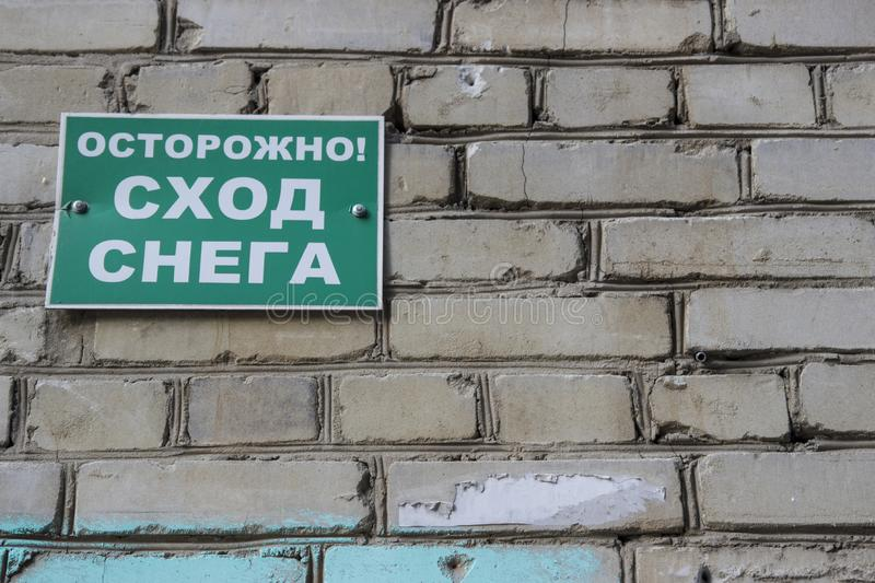 Danger of falling ice and snow: sign. Warning sign in Russian ` Cautiously falling snow from the roof`. Warning sign Danger of falling ice and snow: sign royalty free stock images