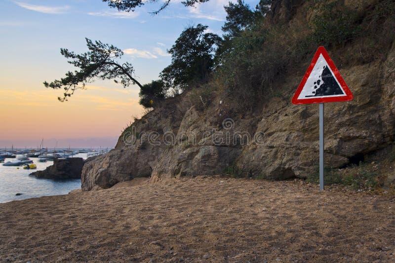 Danger falling rocks sign on Mediterranean beach. Danger falling rocks sign at bottom of pine-clad cliff on he beach at Tamariu, Costa Brava, Catalonia, Spain royalty free stock image