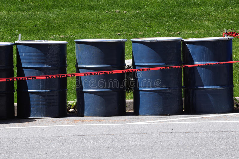 Danger 55 Gallon Drums environmental waste. Danger tape around 55 gallon drums on a paved road near a park in Vancouver Canada royalty free stock photos