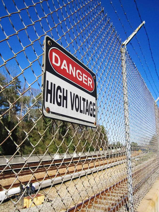 Danger High Voltage Sign along Electrified Rail. Mass, transit, public, transport, transportation, urban, city, commute, commuter, subway, train, track stock photo