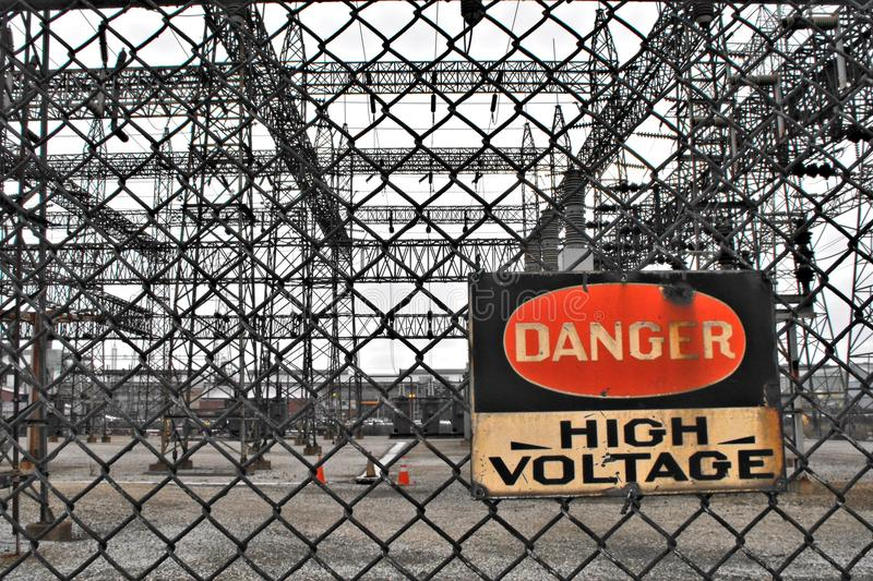 Danger High Voltage. Sign reading, `Danger - High Voltage` displayed on a fence at an industrial power station royalty free stock photos
